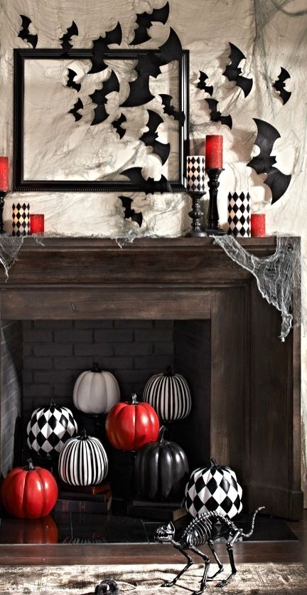 a stylish mantel with bats and red and checked candles and a fireplace filled with checked, striped and red pumpkins