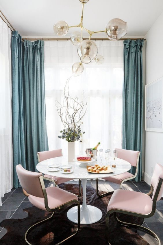 chic pink chairs add color to this glam dining space