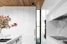 13 a modern all-white kitchen with a marble backsplash and a wooden ceiling