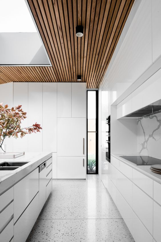 a modern all-white kitchen with a marble backsplash and a wooden ceiling