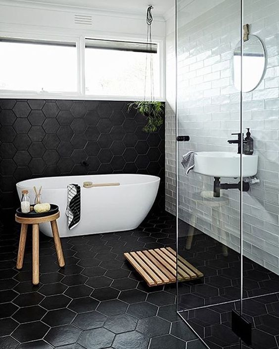 a modern space with subway tiles, black geo tiles, a free-standing bathtub, some wooden touches