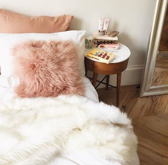 a pink faux fur pillow and a white blanket to add a girlish feel and comfort to the bedroom