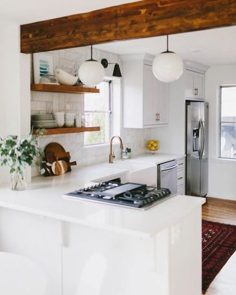 a white L-shaped kitchen spruced up with a wooden beam and shelves is very comfortable for cooking