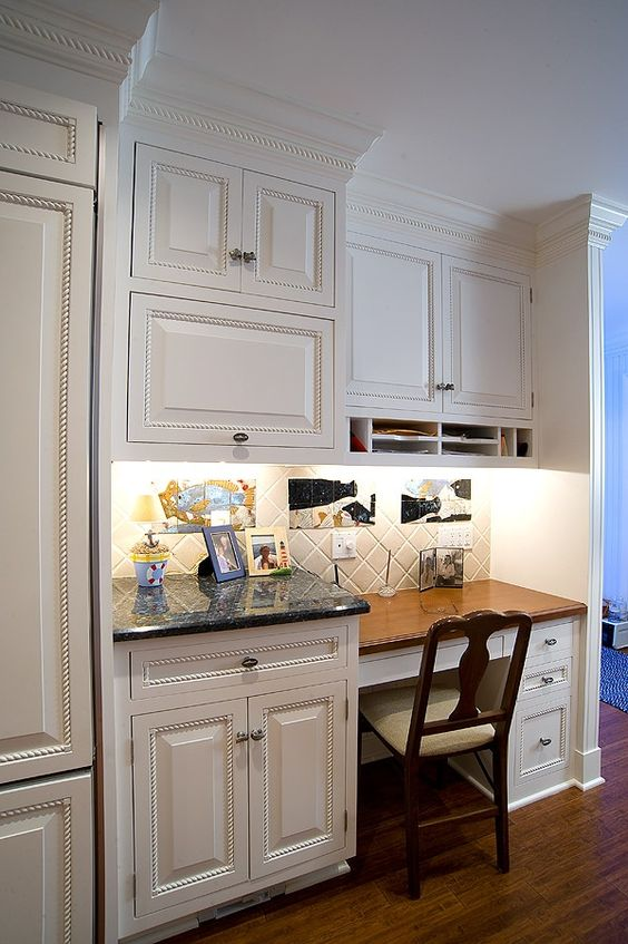 kitchen desk area with traditional cabinets used for document storage