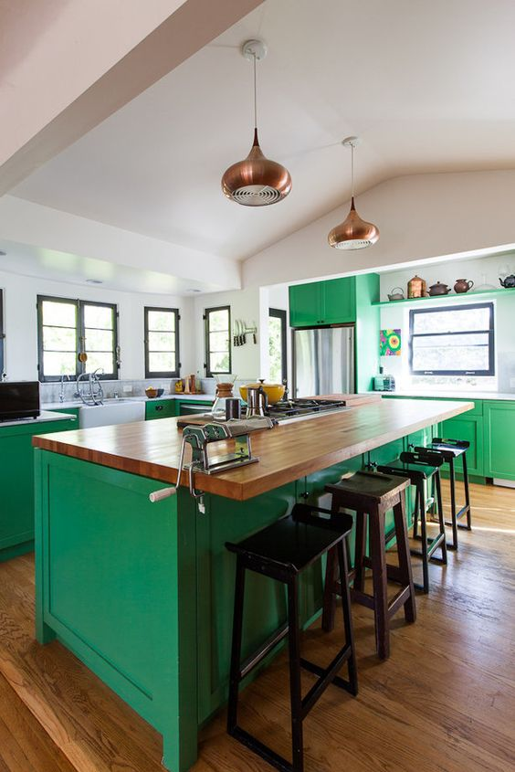 a bold green kitchen is made calmer with neutral countertops and brass touches