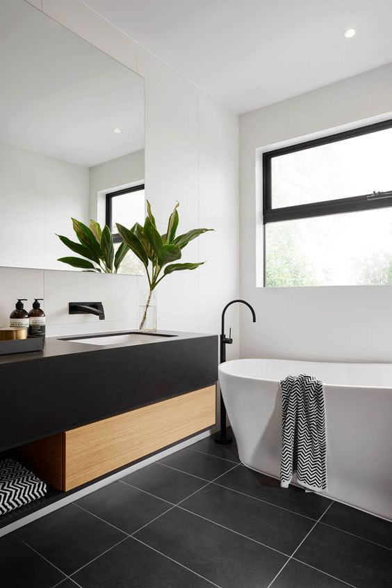 a modern space with a black framed window, dark tiles, a black and wood vanity and a tub