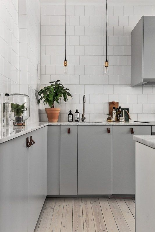 dove grey cabinets, white tiles that cover the whole walls and industrial pendant lamps for a stylish Scandinavian space