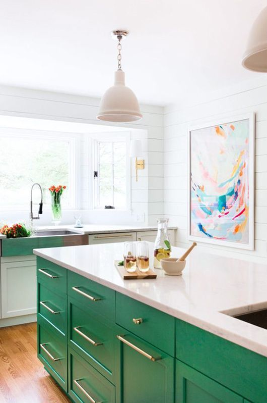 a bold green kitchen island stands out in a neutral space and makes it more cheerful