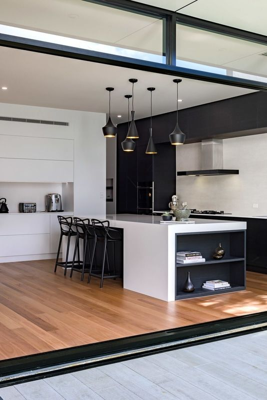 a modern black and white space with sleek cabinets and eye-catchy pendant lamps over the kitchen island