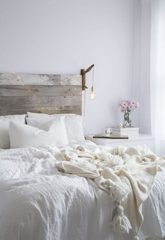 a reclaimed wooden headboard stands out in a neutral space and can be easily DIYed