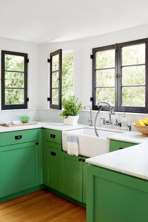 a farmhouse kitchen is added impact with bold sage green color of the cabinets
