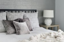 16 a grey bedroom with a white faux fur blanket that makes it more luxurious