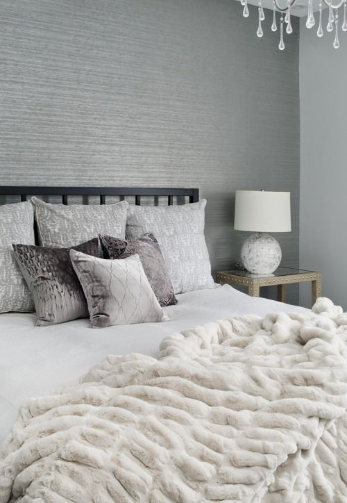 a grey bedroom with a white faux fur blanket that makes it more luxurious