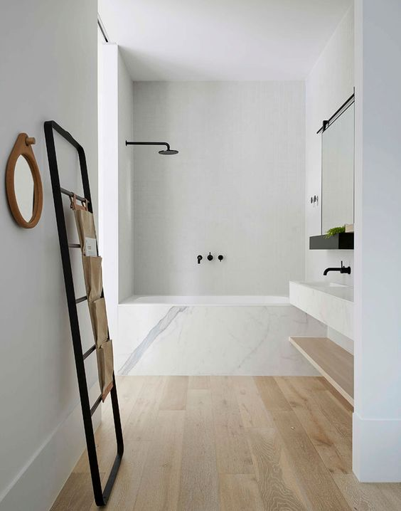 a simple elegant bathroom with wooden floors, a bathtub clad with marble and a marble vanity