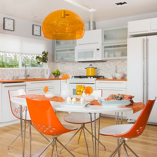 a contemporary kitchen with orange countertops, a lamp and chairs