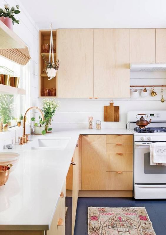 a light-colored wooden L-shaped kitchen with copper details looks warm and very welcoming