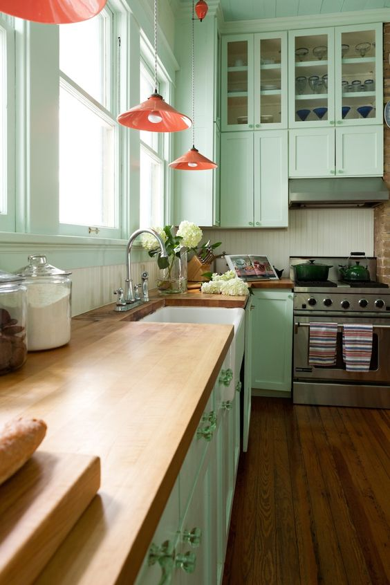a mint green kitchen with coral lamps and natural wood countertops for a vintage feel