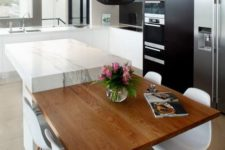 17 a modern black and white kitchen with a marble and wood kitchen island and a pendant lamp