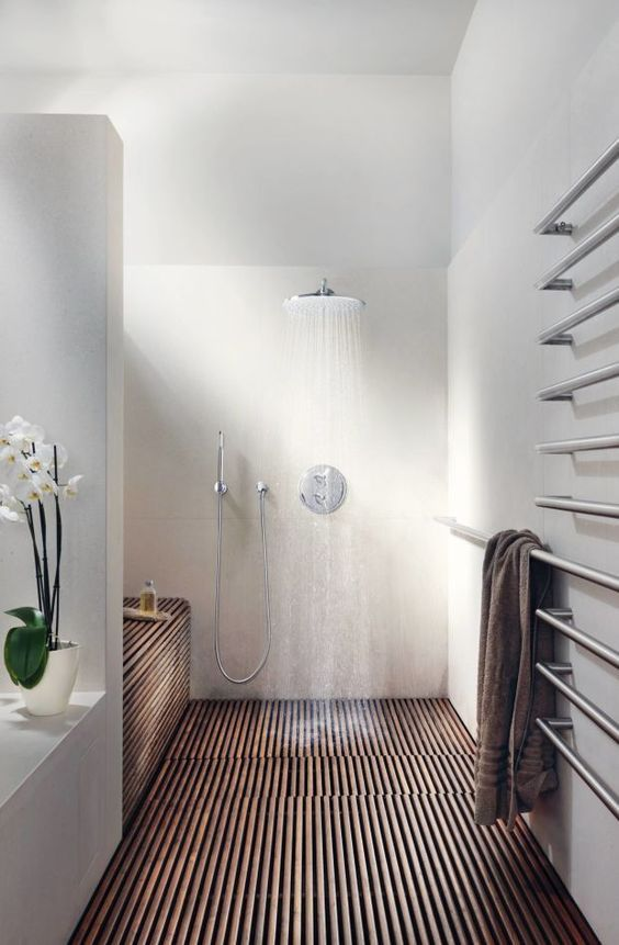 a modern space a with wood clad shower, matte white walls and an orchid for a chic touch