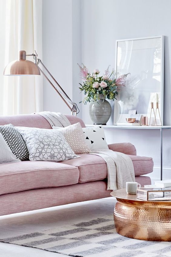 a pink sofa is a perfect piece for a feminine living room, and a copper table and lamp complete the look