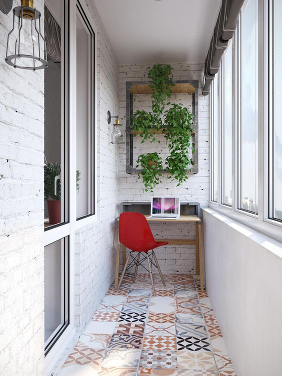 an industrial home office with a small desk, a tile floor and whitewashed brick walls