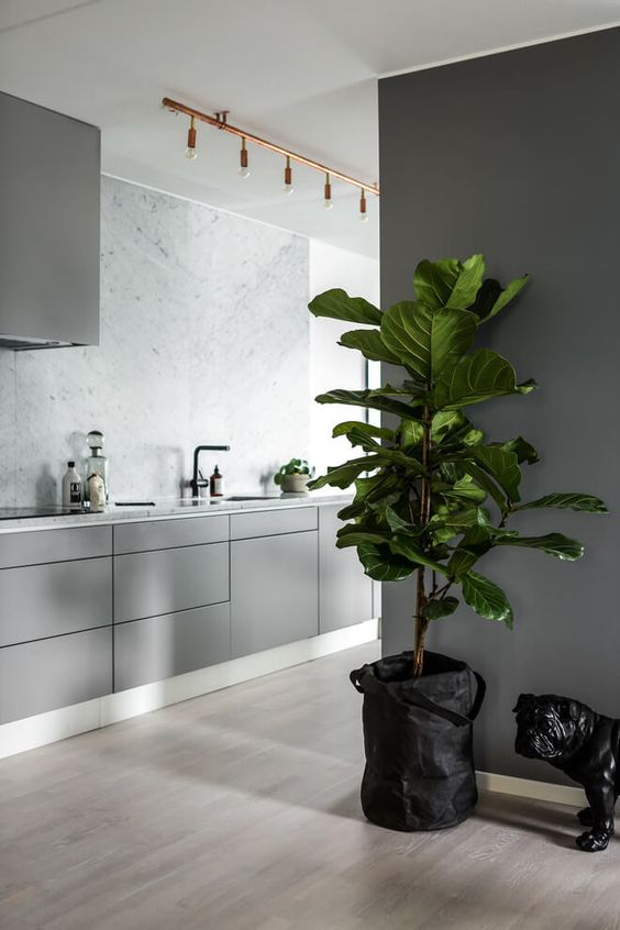 light grey kitchen with a marble wall, copper touches and grey walls for a modern sleek look