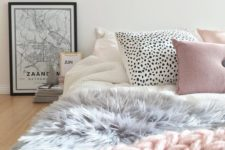 18 a cute girlish bed with a pink chunky knit throw, a faux fur grey blanket and creative printed pillows