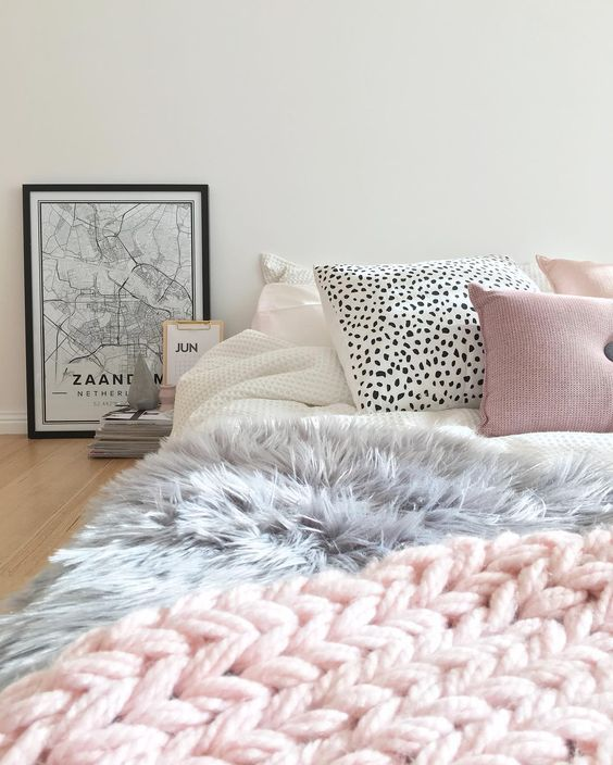 a cute girlish bed with a pink chunky knit throw, a faux fur grey blanket and creative printed pillows