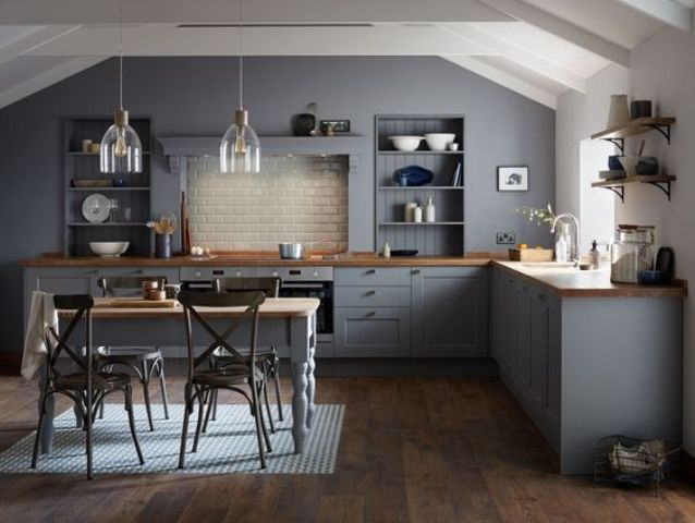 a dark grey vintage kitchen with wooden countertops and a matching dining table, which doubles as a kitchen island