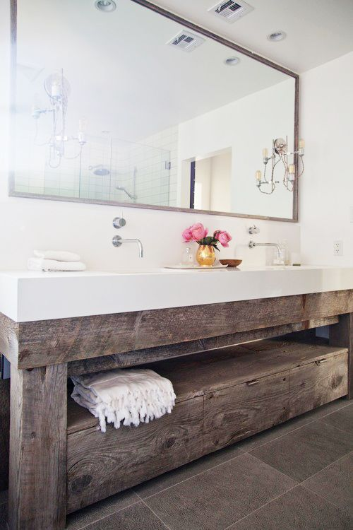 a large reclaimed wood vanity with a white countertop looks very modern and cozy