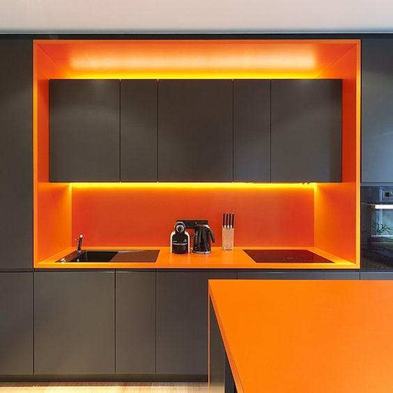 a minimalist grey kitchen with bold orange countertops, lights and a backsplash