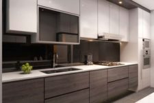 19 a contrasting kitchen with white and wooden cabinets and a sleek black glass backsplash