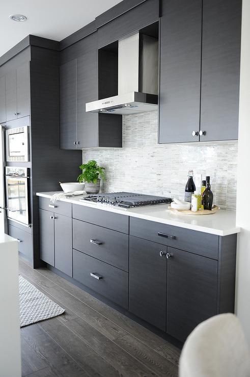a dark grey kitchen with a light tile backsplash and white counters looks edgy and chic
