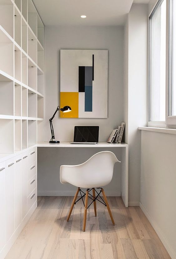 a minimalist home office with a large built in shelving unit and desk