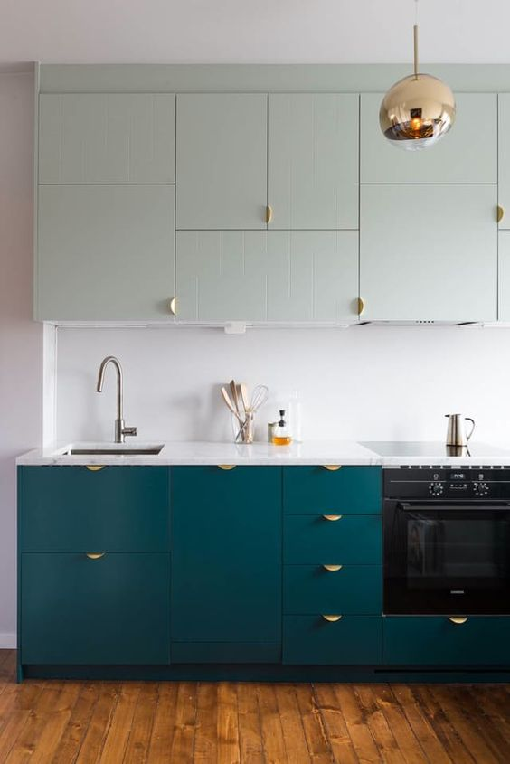 a modern kitchen with teal floor cabinets and very pale green ones above looks bold and very interesting