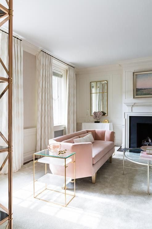 a modern serene living room with a geometric blush sofa and brass touches