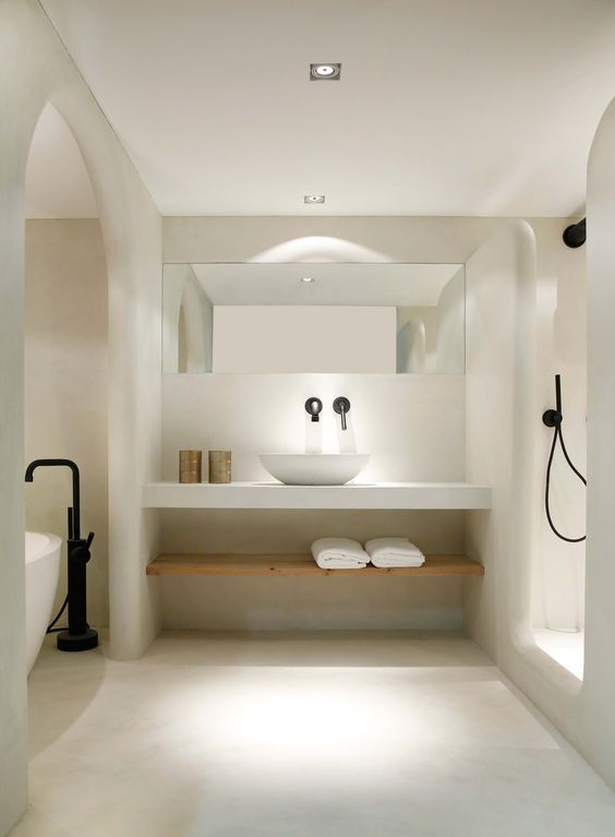a neutral space decorated with light-colored stone, a black faucet and a free-standing tub and a vanity shelf