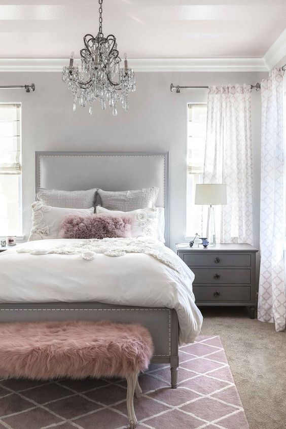 a chic grey bedroom is enlivened with a faux fur dusty pink bench and a matching pillow