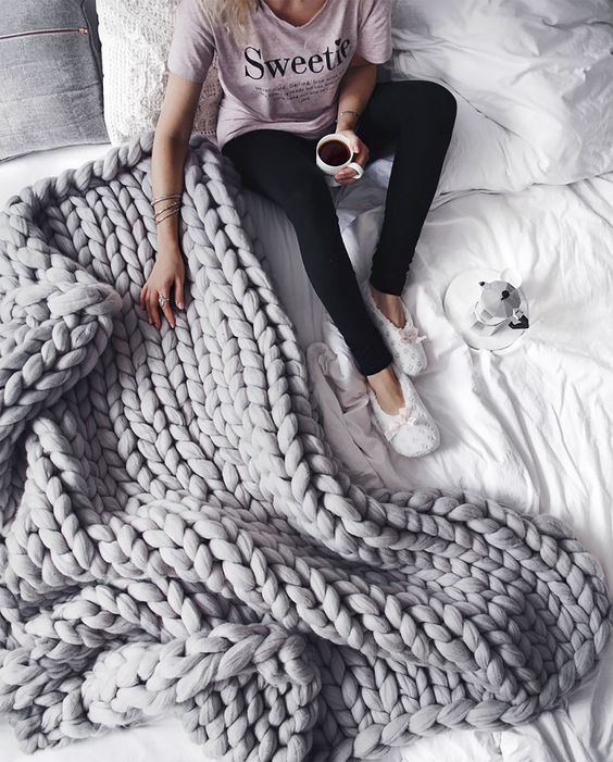 a grey chunky knit blanket will add warmth and a textural touch to your bed
