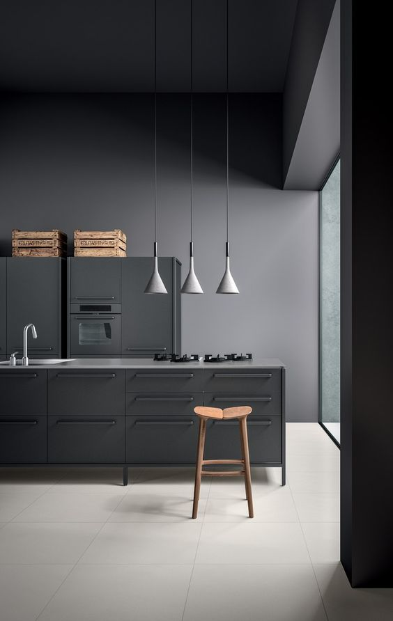 a grey metal industrial kitchen with crates and pendatn lamps done in concept of a moody space