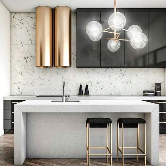 a modern space with black metal cabinets, white stone counters and a backsplash and a unique brass hood
