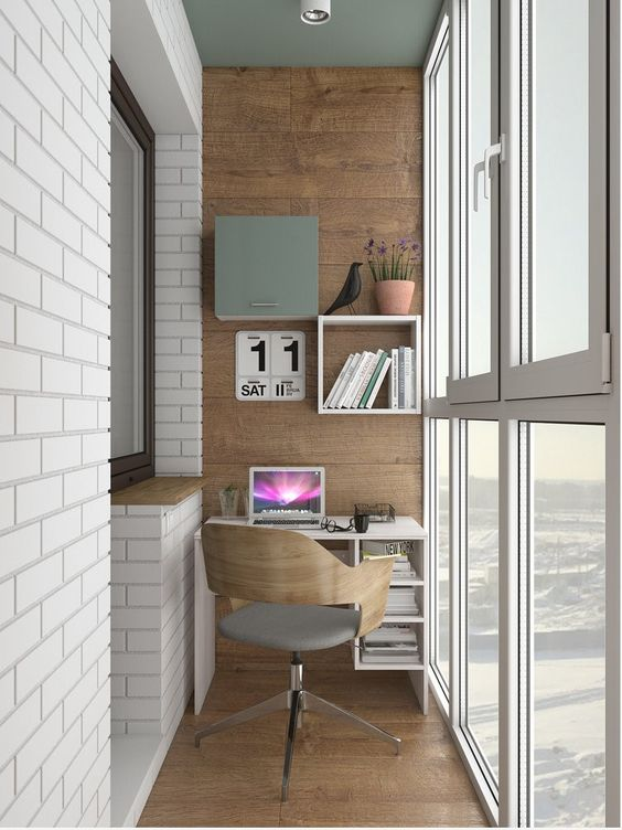 an industrial home office with a small desk, built in shelves and a modern chair