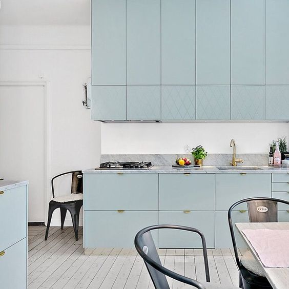 a beautiful aqua-colored kitchen with lots of cabinets and whitewashed wooden floors for a light feeling