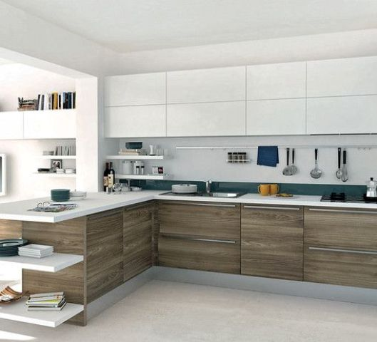 a bold white and wood L-shaped kitchen with teal touches and bookshelves to divide the spaces