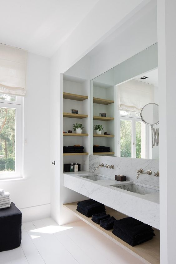 a functional sink space with white marble, wooden shelves and a large mirror