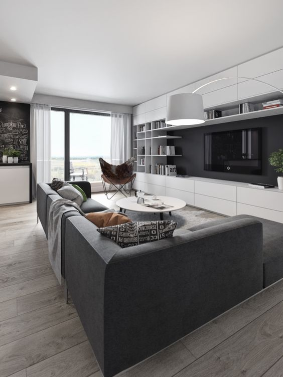 a monochrome black and white living room with a large setional sofa and a wall storage unit