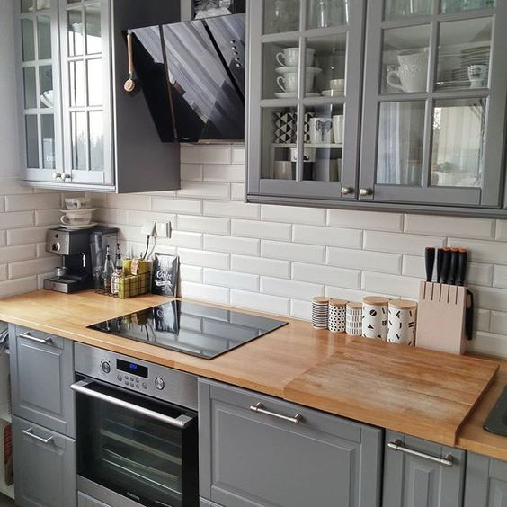 A Vintage Grey Kitchen With Wooden Countertops And White Subway Tiles