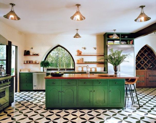 bold green cabinets and a kitchen island are balanced with metalllic lamps and wooden countertops