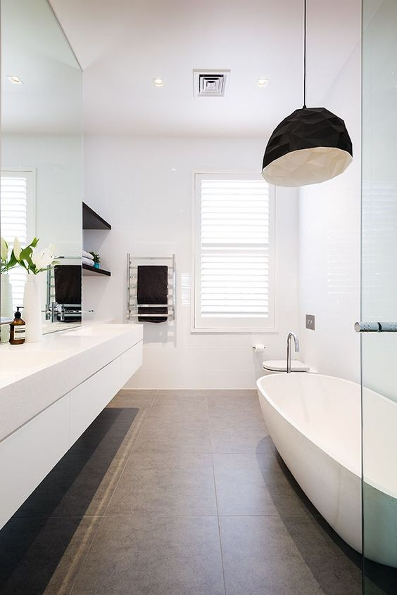 the bathroom is made more interesting with black shelves, a black faceted lamp and a large bathtub