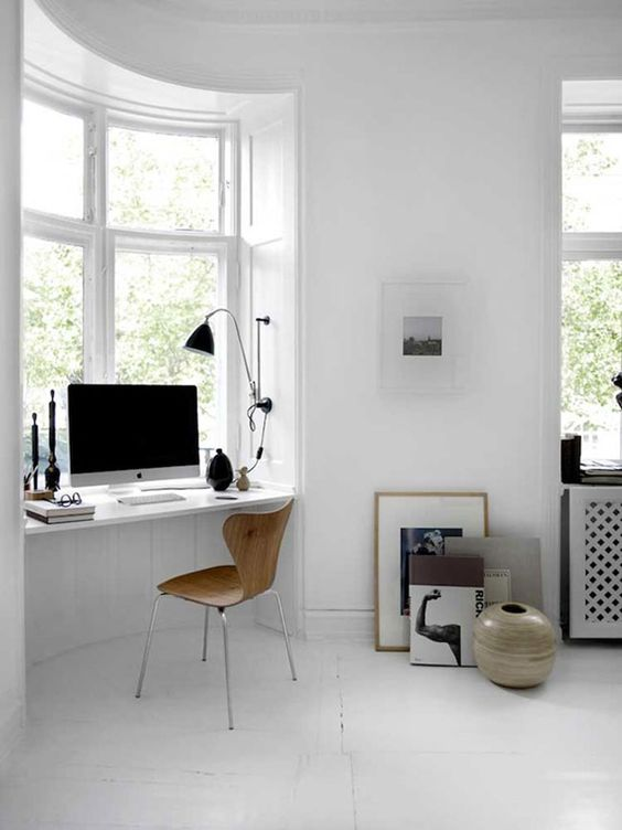 a Scandinavian bedroom windowsill is used as a home office space